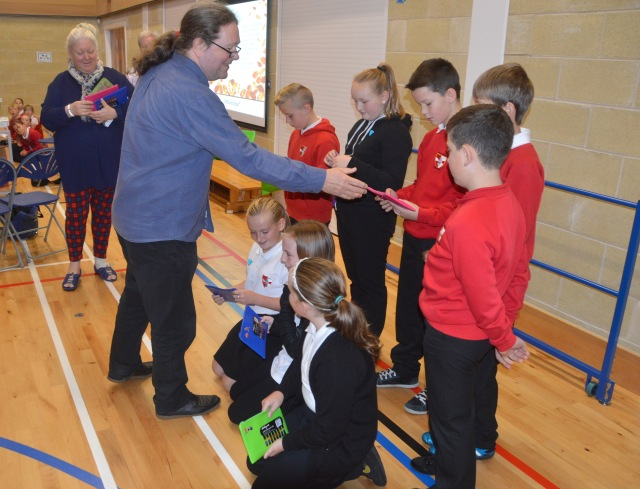 Neil and Vic hand over gifts to grateful pupils